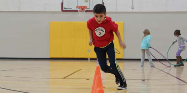 Boy Running Cones in Gym