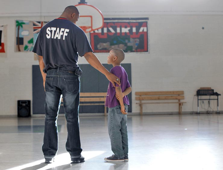 Staff and Young Boy on Basketball Court